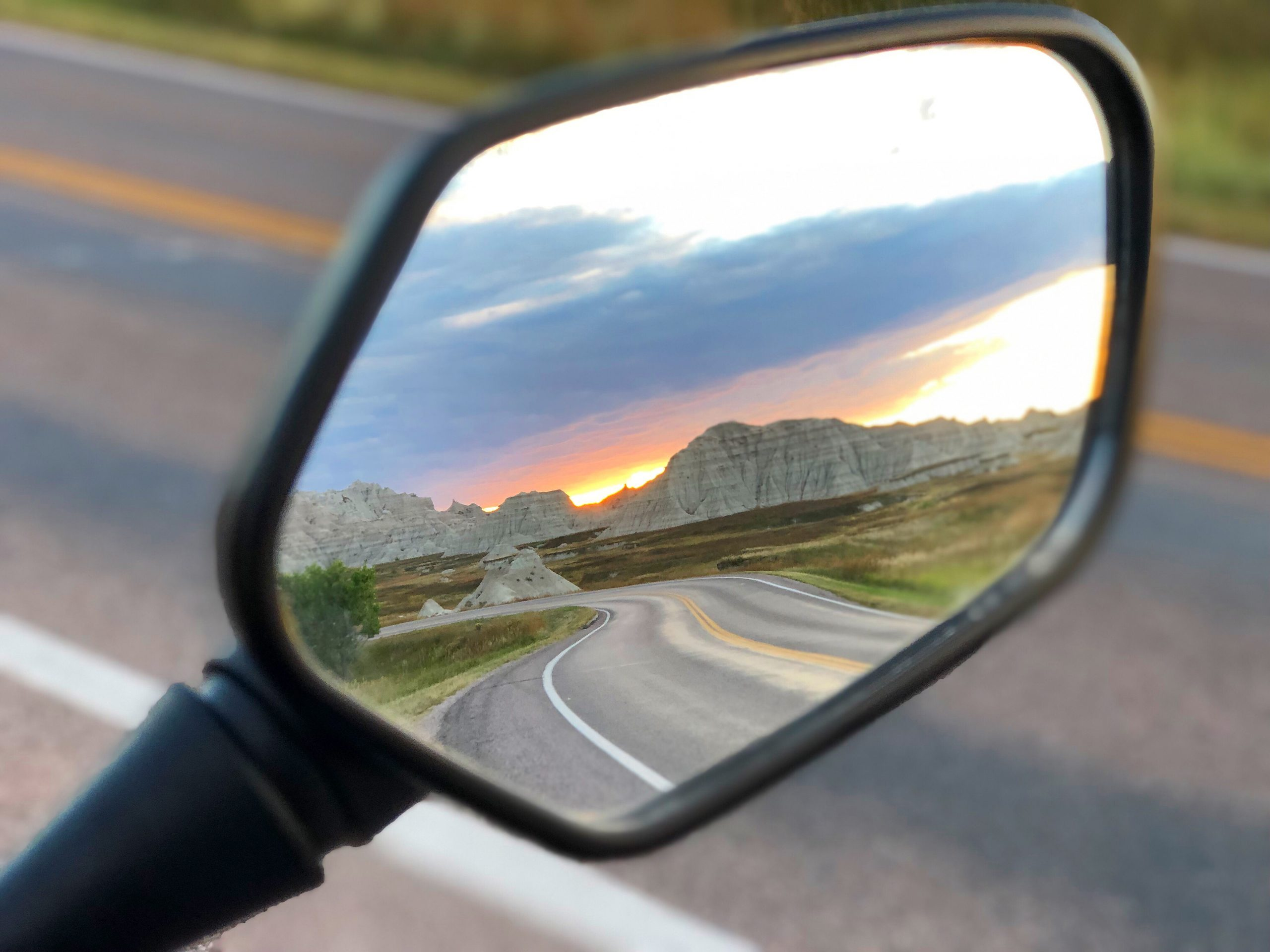 Sunset in the Badlands NP through the sideview mirror